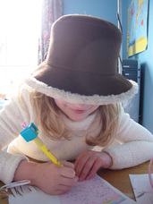 Young girl in hat writing